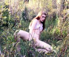 Pelirroja saca un consolador y se masturba entre los arbustos